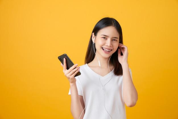 幸せなアジアの女性がスマートフォンを押しながら音楽を聴く