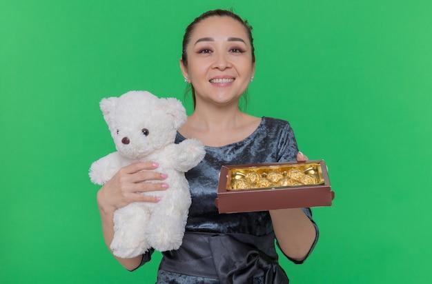 緑の壁の上に立っている国際女性の日を元気に祝って笑顔の贈り物としてテディベアとチョコレート菓子の箱を持って幸せなアジアの女性