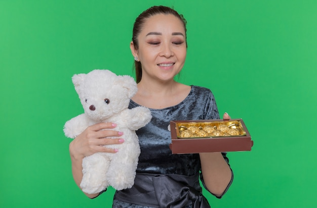 Happy asian woman holding teddy bear and box of chocolate candies as a gifts smiling cheerfully celebrating international women's day standing over green wall