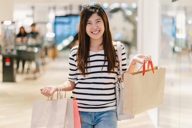 행복 한 아시아 여자 쇼핑 가방을 들고 새로운 패션 옷을 찾고
