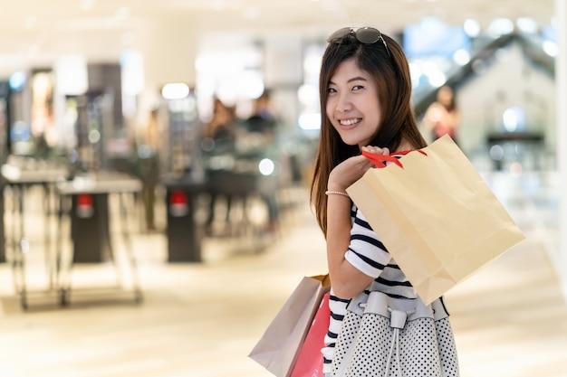 도시 백화점에서 쇼핑 가방을 들고 행복 아시아 여자