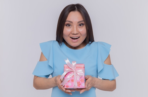 白い壁の上に立って国際女性の日を元気に祝って笑顔でプレゼントを保持している青いドレスを着た幸せなアジアの女性