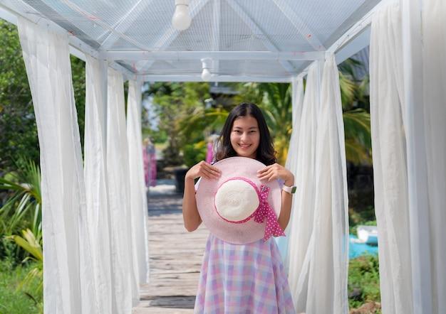 Счастливая азиатская женщина в повседневном платье, держащая шляпу в арке, украшенной белой занавеской в саду