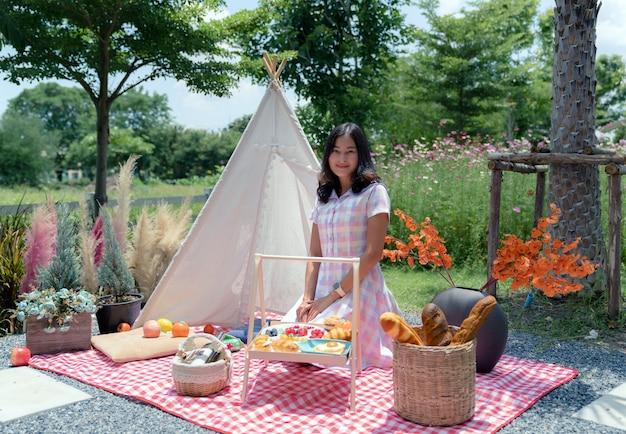カジュアルなドレスを着た幸せなアジアの女性は、庭の白いテントで飾るピクニックセットの布マットの上に座って、女の子は休暇でリラックス