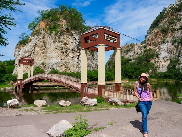 태국 라차부리의 공공 바위산 공원에 화려한 조끼를 입은 행복한 아시아 여성, 다리 레이블에 있는 편지는