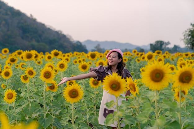 귀여운 드레스와 펠레 모자를 쓴 행복한 아시아 여성은 저녁에 피는 노란 해바라기 정원과 함께 즐깁니다.
