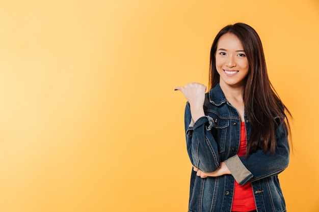 Счастливая азиатская женщина в куртке джинсовой ткани указывая прочь на copyspace
