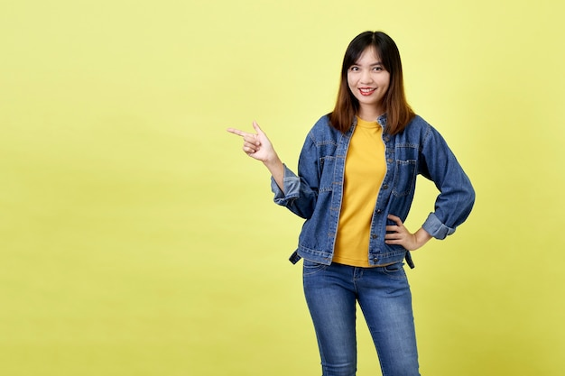 Счастливая азиатская женщина в джинсовой куртке указывает сторону, чтобы скопировать пространство и смотрит в камеру над желтым пространством