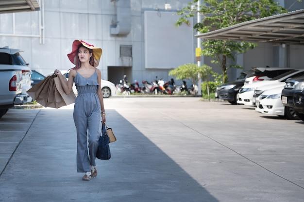 ショッピングバッグとファッションカジュアルドレスの幸せなアジアの女性は、駐車場で歩く。