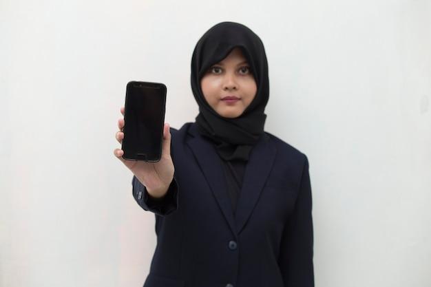 웃는 소녀의 모바일 휴대 전화 초상화를 보여주는 hijab에서 행복 한 아시아 여자