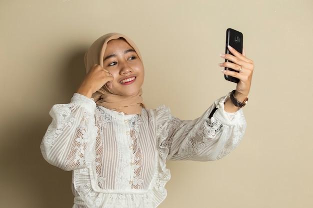 携帯電話で自分撮りをするヒジャーブで幸せなアジアの女性。