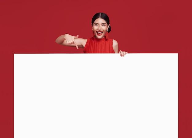 Счастливая азиатская женщина в красной повседневной одежде с рукой, указывающей пустой баннер объявления в красном
