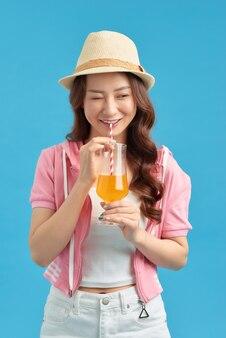 青い背景に新鮮なフルーツジュースの飲み物のガラスと夏のカジュアルな服を着て幸せなアジアの女性