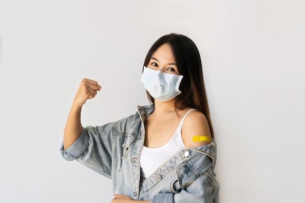 白い背景にコロナウイルスワクチン注射後の絆創膏で腕を示すサージカルマスクの幸せなアジアの女性。抗ウイルス免疫化の概念。スペースをコピーします。