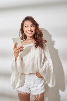 흰색 배경 위에 카메라를 보면서 스마트 폰을 들고 기뻐하는 최신 유행의 옷에 행복 아시아 여자