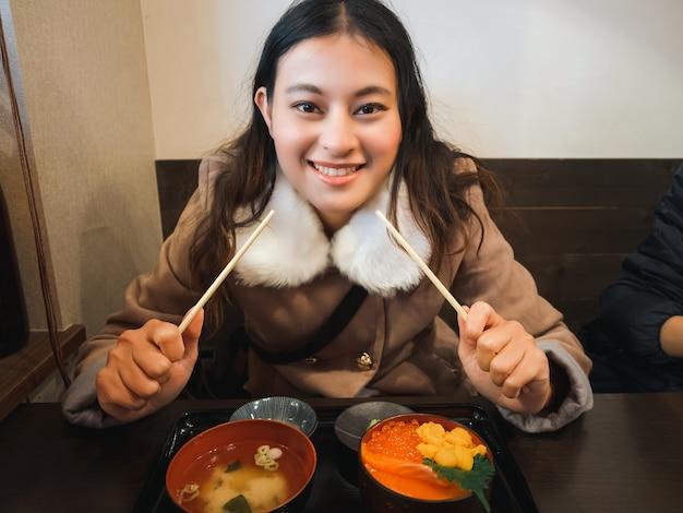 Счастливая азиатская женщина в зимнем пальто, держащая палочки для еды за деревянным столом с японской рисовой миской в ресторане, девушка наслаждается едой