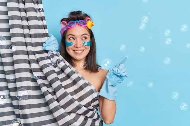 Happy asian woman indicates at copy space applies collagen patches under eyes hair rollers takes douch enjoys showering points at upper right corner against blue wall with bubbles around