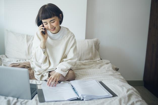 Счастливая азиатская женщина использует компьтер-книжку, smartphone для разговаривать с ее боссом. она работает из дома.