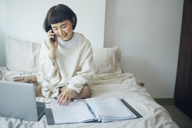 Happy asian woman is using laptop, smartphone for talking with her boss. she work from home.