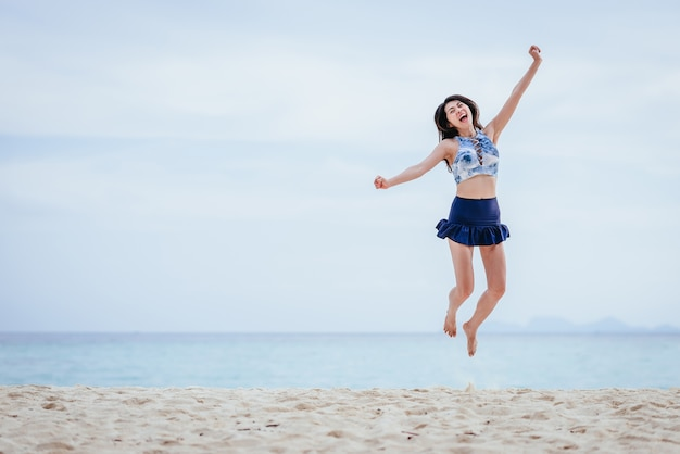 Happy asian woman jumping on the beach