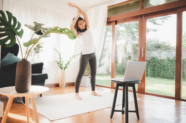 幸せなアジアの女性は運動を伸ばすオンライントレーニングを学びました