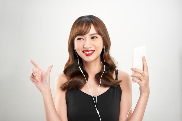 ヘッドフォンで音楽を聴いて幸せなアジアの女性。若い新鮮なアジアの女性モデル