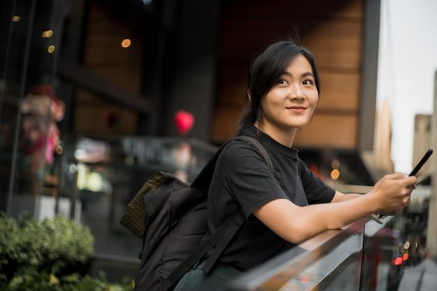 도시에서 그녀의 전화를보고 행복 한 아시아 여자