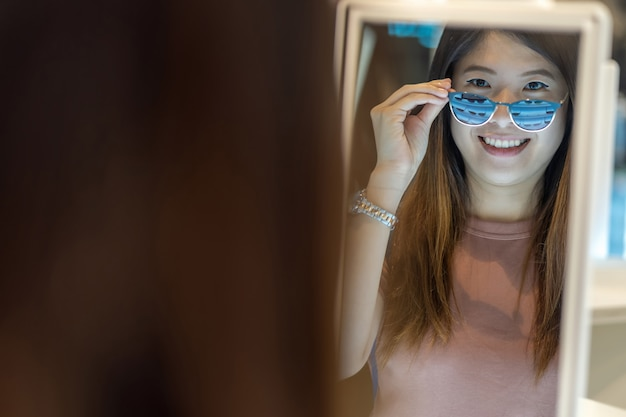 Happy asian woman looking and choosing eyeglasses in store shop at department store
