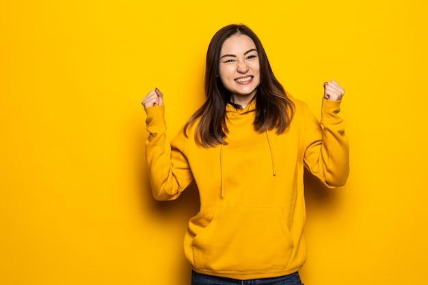 Счастливая азиатская женщина делает выигрышный жест, изолированный над желтой стеной