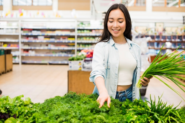Happy asian woman picking greenery in grocery store