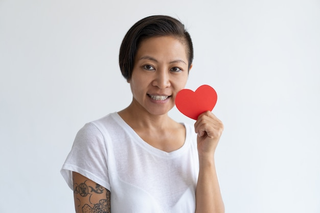 Happy asian woman posing with paper heart
