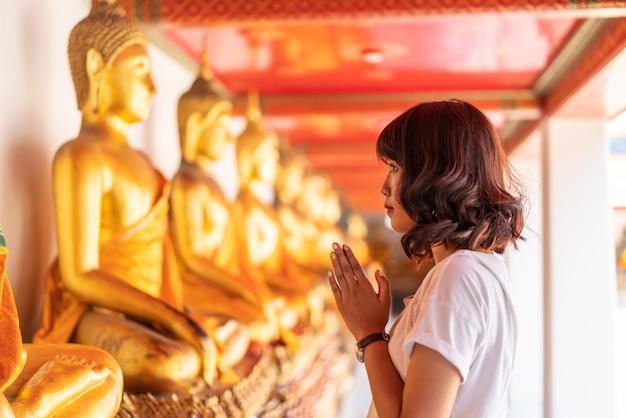Happy asian woman praying with buddha