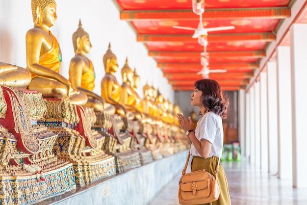 Счастливая азиатская женщина молится с буддой