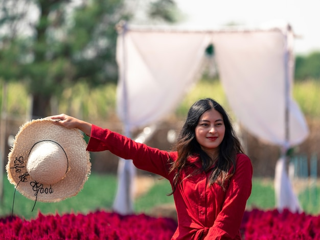 Happy asian woman in red dress in red flower garden holding hat