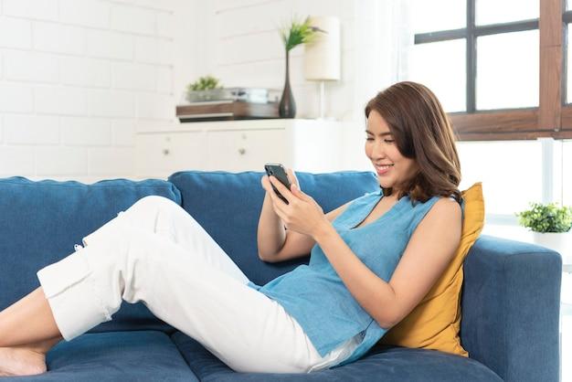 Felice donna asiatica che si distende sul comodo divano utilizzando smartphone in chat nei social network, guardando video divertenti a casa.