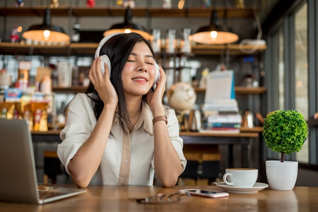 Happy asian woman relaxing and listening music in coffee shop with computer laptop