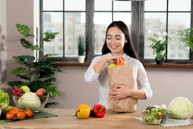 Happy asian woman removing vegetables from grocery bag on wooden kitchen counter