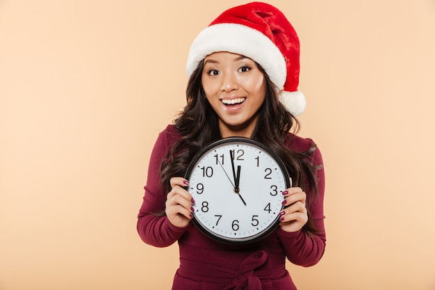 Happy asian woman in santa claus red hat holding clock showing nearly 12 celebrating new year eve over peach background