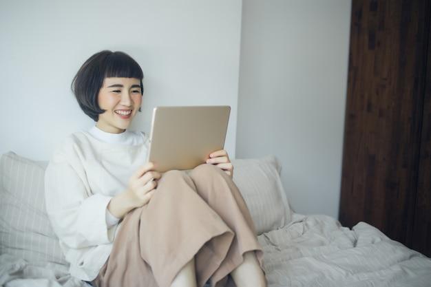 Счастливая азиатская женщина видя netflix на спальне.