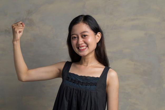 拳を示して、勝者のジェスチャーを作る幸せなアジアの女性