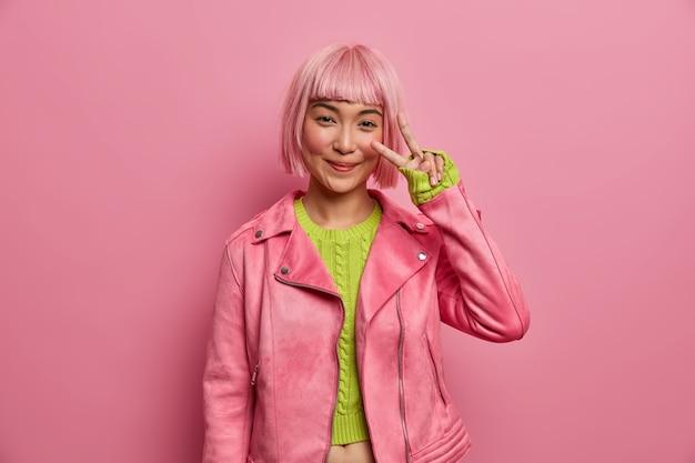 행복 한 아시아 여자는 v 기호를 보여주고, 시원하고 긍정적이며, 세련된 분홍색 재킷, 녹색 스웨터를 입고, 승리를 즐기고, 적극적으로 몸짓을합니다.