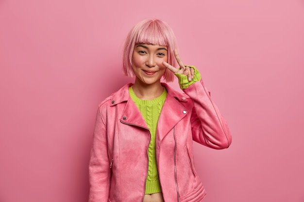 La donna asiatica felice mostra il segno v, rimane fresca e positiva, vestita con una giacca rosa alla moda, un maglione verde, gode della vittoria, gesticola attivamente