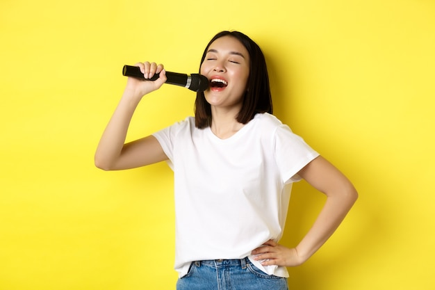 幸せなアジアの女性がカラオケで歌を歌い、マイクを持って、黄色の背景の上に立っています。
