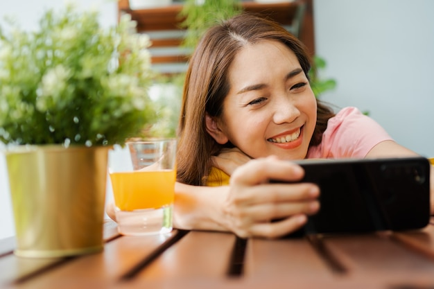 Happy asian woman sitting in the backyard and holding smartphone for watching a movie series during relax time.