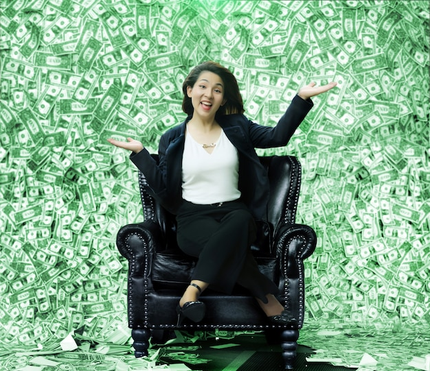 Happy asian woman sitting on a chair full of money like a millionaire from winning the lottery or business rewards