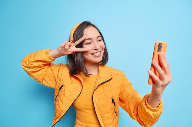 Счастливая азиатская женщина с радостью улыбается, делает мирный жест поверх глаз, принимает селфи. современный смартфон слушает музыку через стереонаушники, изолированные на синей стене. технологии образа жизни