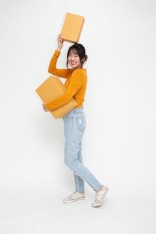Счастливая азиатская женщина улыбается и держит коробку посылки пакета, изолированную на белом фоне, концепция службы доставки и доставки, полная длина людей