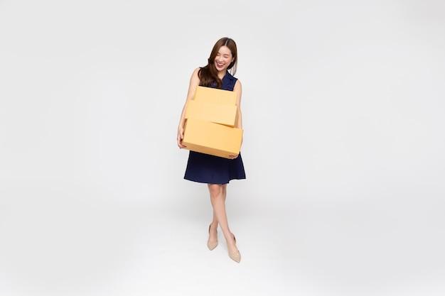 Счастливая азиатская женщина улыбается и держит пакет посылку на белом фоне
