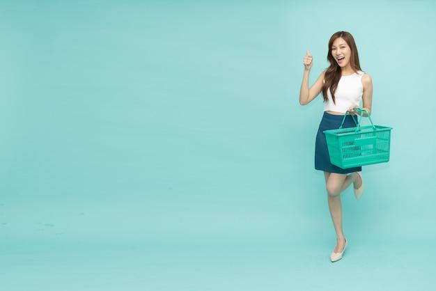 밝은 녹색 배경에 격리된 쇼핑 바구니를 들고 웃고 있는 행복한 아시아 여성