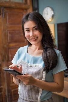 그녀의 집에서 그녀의 온라인 메시지를 확인하기 위해 그녀의 전화를 들고 카메라에 웃고 행복 아시아 여자